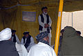 Haji Faizal Mohammad, standing, the governor of the Panjwai district of Kandahar province, Afghanistan, speaks with 30 area farmers during an agricultural shura, or meeting, at Combat Outpost Mushan in the 130328-A-ZZ999-748.jpg