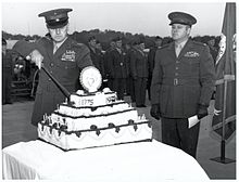 In front of a group of men, a man cuts a cake with a sword while a second man looks on