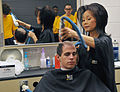 Hyong Davis, right, gives a U.S. Navy recruit his first haircut inside the Golden 13 Recruit Inprocessing Center's Navy Exchange Barber Shop at Recruit Training Command (RTC) at Naval Station Great Lakes, Ill. 121120-N-IK959-840.jpg