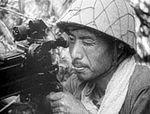 Japanese soldier firing a Type 92 heavy machine gun, aiming through telescopic sight.jpg