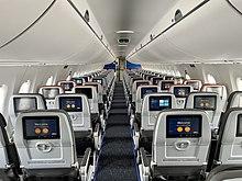 Viene mostrato l'interno di un aereo, con due posti per fila a sinistra e tre posti per fila a destra.  Ogni posto ha anche uno schermo televisivo personale di fronte ad esso.  Lo schema generale dei colori è grigio.