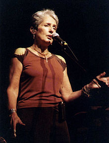 Baez at microphone, without guitar, in sleeveless top, open left hand extended waist high