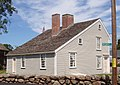 A gray saltbox with white trim is seen at an angle from the rear. A low stone wall stands in the foreground.