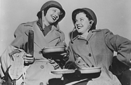 Two woman leaning toward each other are laughing and dressed in World War II oversized military coats and helmets
