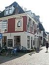 foto van Hoekpand onder zadeldak met schild aan de zijde van de Grote Kerkstraat