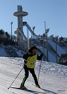 Special Olympics-utøver foran hoppbakkene i Alpensia Resort.Foto: Korean Culture and Information Service (2013)
