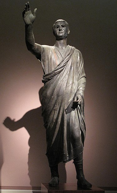 "The Orator, c. 100 BC, an Etrusco-Roman statue of a Republican senator, wearing toga praetexta and senatorial shoes; compared to the voluminous, costly, impractical togas of the Imperial era, the Republican-era type is frugal and ""skimpy"" (exigua). L'Arringatore.jpg"