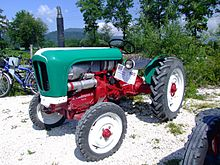 A green and red 1951 Lamborghini farm tractor parked in a gravel patch with trees and hills in the background