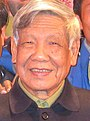 An old graying man wearing a brown buttoned-up jacket, and a pale green shirt
