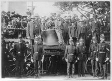 The Liberty Bell on a wagon, a number of people, including policemen, pose with it.