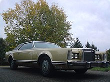 Front quarter view of a coupé parked in an open outdoor setting. The automobile is a sand Lincoln Continental Mark V.