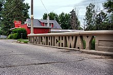 "A small concrete bridge crosses a stream.  The sides of the bridge were designed to spell out ""Lincoln Highway""."