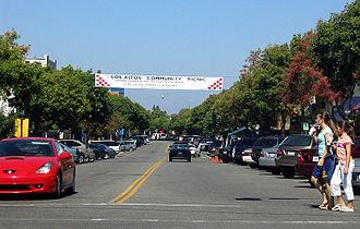 Los Altos, California - An intersection in downtown Los Altos, with features like tree-lined sidewalks, diagonal parking, small shops, and banners advertising community events.
