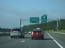 Ground-level view of three lanes of a divided expressway; two large green exit signs are visible in the distance, and the road is surrounded by dense forests.