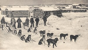 Early 20th century view of Circle City, as a sled dog team prepares to leave for Fort Gibbon with the mail.