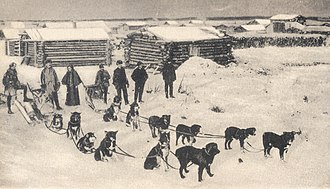 Circle, Alaska - Early 20th century view of Circle City, as a sled dog team prepares to leave for Fort Gibbon with the mail.