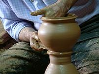 A man shapes pottery as it turns on a wheel. (...