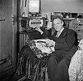 Man zittend op de bedbank terwijl hij de radio bedient en in een boek bladert, Bestanddeelnr 252-9335.jpg