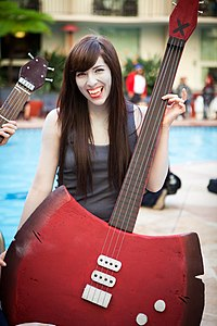 A woman, dressed in a grey shirt holding a red axe-bass hybrid.