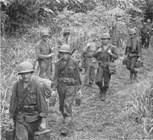 Black and white photo of four men wearing military uniforms and helmets carrying bags and boxes along a trail. Several other men are standing at the edge of the trail, and behind them.