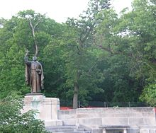 Large bronze statue of man carrying a cross, surrounded by trees.