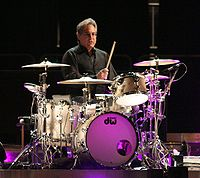 Gray haired man in a black shirt sitting behind a drumset
