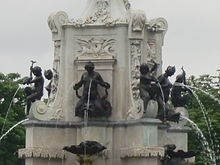 six black statues on an ornate white stone structure. Waterjets are emerging from their nipples and various other places