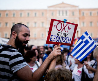 "2015 Greek bailout referendum - A ""No"" campaigner outside the Greek parliament building on 29 June 2015, holding a sign reading ΟΧΙ ΣΤΗΝ ΕΞΟΝΤΩΣΗ (""no to annihilation"")."