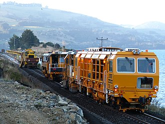 KiwiRail - KiwiRail Network replacing sleepers on the Main South Line at Blueskin Bay, Otago. Closest machine is a dynamic track stabiliser, followed by a Regulator, then a Continuous Action Tamper.