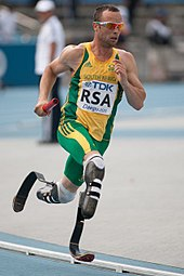 A disabled Caucasian sprinter running on running blades, he wears the green and yellow of South Africa.