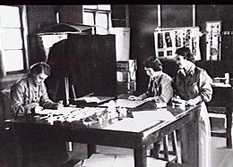 Three women in overalls around a large desk
