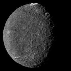 A round spherical body with its left half illuminated. The surface is dark and has a low contrast. There are only a few bright patches. The terminator is slightly to the right from the center and runs from the top to bottom. A large crater with a bright ring on its floor can be seen at the top of the image near the terminator. A pair of large craters with bright central peaks can be seen along the terminator in the upper part of the body. The illuminated surface is covered by a large number of craters.
