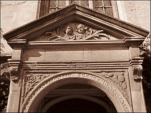 "Part of a stone doorway. The top is triangular, with the heads of two cherubs in the panel beneath. On the curved arch immediately above the entrance, the words ""Ascendat oratio descendat Gratia""; a rose and a thistle on the adjoining panels"