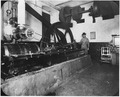 Photograph of a San Francisco Mint employee at the steam engine in the basement area of the Mint. - NARA - 296562.tif