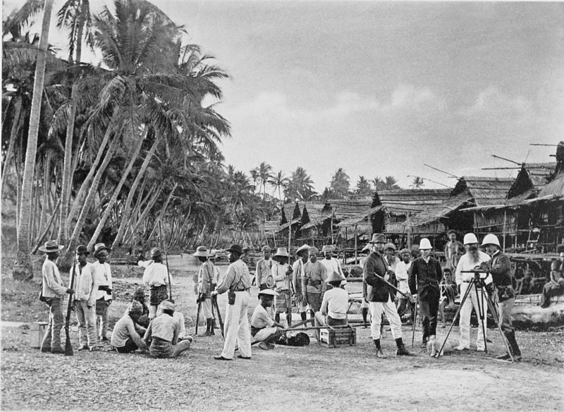 Black and white photograph of 4 Europeans, 3 in pith helmets, standing round a theodolite. The 20 or so Malays are wearing an assortment of sun-protective headgear.