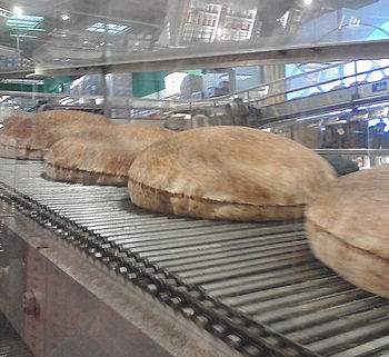 Puffed up, freshly baked pita bread on a conve...