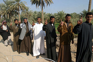 Iraqi parliamentary election, December 2005 - A group of Iraqi citizens walking down a path showing their purple fingers, signifying that they had voted.