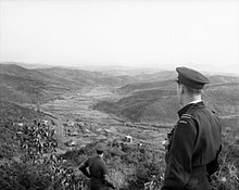 Man in dark-coloured military uniform and peaked cap looking over a valley