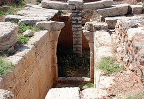 A corridor built of ashlars leads to a ruined archway