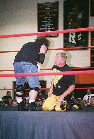 Shane Douglas - Douglas (kneeling) wrestling against Raven