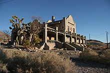 An ornate, two-story masonry building rests under a cloudless blue sky in a setting of gravel, two spiny trees, and many low shrubs. Its windows are boarded.