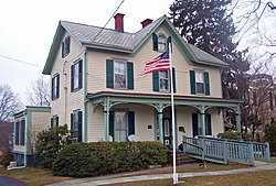 A pale yellow two-story wooden house with a pointed roof and ornate green trim. An American flag flies in front