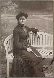 The photograph of a woman wearing pince-nez glasses seated on an outdoor bench holding a lorgnette