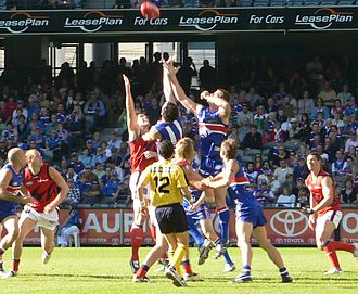 Ruckman (Australian rules football) - A Western Bulldogs player rises over the top of the two designated ruckman to employ a tandem ruckwork strategy in an AFL match at the Telstra Dome in Melbourne.