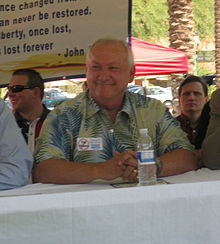 A smiling, somewhat heavy-set man in his sixties with thinning white hair and wearing a green and blue floral print shirt sits behind a table under a covering outdoors. On his shirt is a sticker saying no to tax hikes and in front of him is a bottle of water. Several other men are sitting near him; in the background is a sign with a quotation about liberty from John Adams, some cars in a parking lot, and tall palm trees.