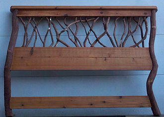 Rustic furniture - Rustic headboard for a queen size bead with cedar and mountain laurel branches and posts.