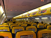 Ryanair cabin, with advertising on overhead lockers and safety cards on seatbacks