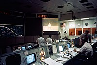 Several rows of consoles. A large screen showed a lunar lander
