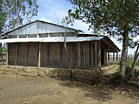 One-room schoolhouse with woven bamboo walls and corrugated tin roof