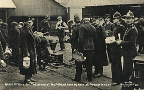 Rescue workers and police standing at the pithead. Some of the men are tending a coffin